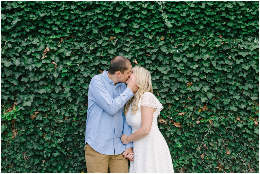 couple kissing in front of vine wall at longwood gardens