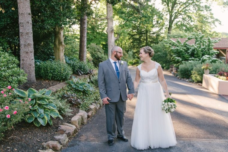 bride and groom walking into sunlight at meredith manor