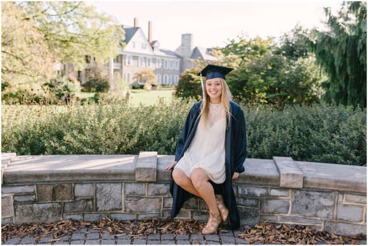 penn state university senior sitting on wall in gown