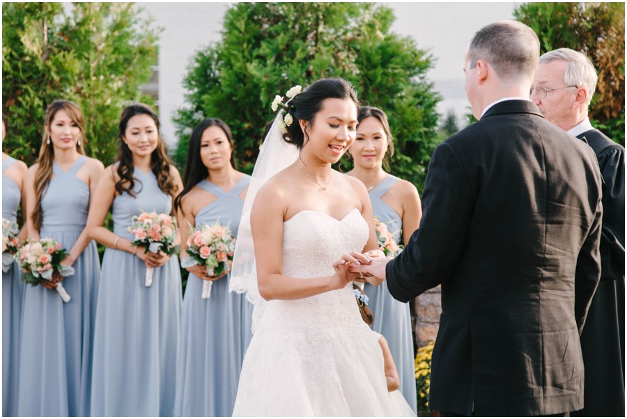 bride placing ring on grooms finger at Executive Banquet and conference center