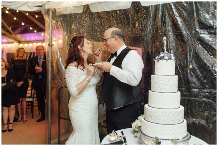 couple eating master bakers cake at loch aerie mansion wedding frazer pa